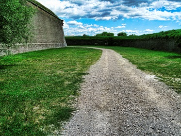 Gravel Road Path Near Castle Wall With Blue Sky